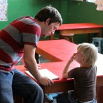 Joshua helps a child at INABIF. Josh has learned that working with children requires calm, patience and energy.