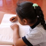 A student concentrates on her writing.
