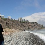 Jake checks out the rocky beach. In the background: high-rise apartment buildings in the Miraflores district.