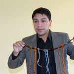 Amadeo Valer Farfán shows a replica of a quipu, an Inca counting device.
