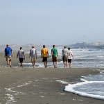 Goshen College men stroll down the beach.