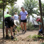 Maria and other students begin pulling weeds in the garden.