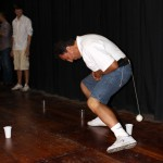 Eduardo Nue Pereda, Jake's host father, tries to knock over cups with a tennis ball attached to a string that is tied to the back of his belt.