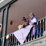 Two members of a group watch the spectacle from a balcony overlooking the Plaza de Armas.