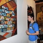 Jake examines a painting by Victor Delfin.