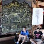 Thomas and Caleb beside a painting that depicts a tuberculosis outbreak in a Lima shantytown.