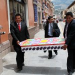 Two men carry a retablo, a type of cabinet which contains pottery figures, down an Ayacucho street.