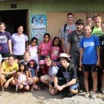 Goshen College students pause for a group photo with  Corpusa Villavicencio Zela and her children in the Chavín de Huántar neighborhood of Villa El Salvador.