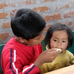 A young boy gently and patiently feeds lunch to his little sister.