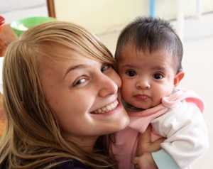 Aimee cuddles with a cute baby in the orphanage.