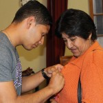 Alejandro pins a Goshen College button on his host mother's sweater.
