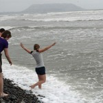 Emma  wades into the Pacific Ocean followed by Leah, Lucas and Joel.