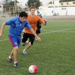 A Peruvian student and Derek seek control of the ball.