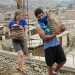 Emma and Alejandro carry bags of rocks.