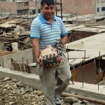 Peru SST Service Coordinator Willy Villavicencio carries a bag of rocks.