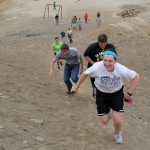 Jaime, Tim, Michael and other students sprint toward the summit of a small mountain at Puente Piedra.