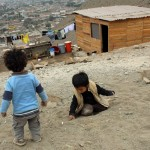 Children play beside a newer home in Puente Piedra.