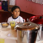 A girl pauses while eating lunch.