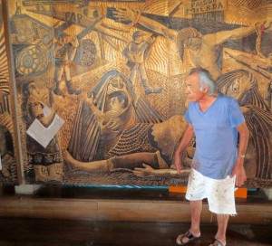 Peruvian artist Victor Delfin poses in front of his huge wood carving depicting atrocities on both sides of the Shining Path war.