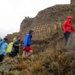 Damp but undeterred, these students climbed to the Inca storehouses, seen in the background.