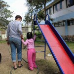 Jaime guides a child with physical limitations who is learning to walk.