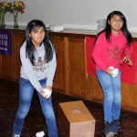 "Derek Peter's host sisters, Galeth and Zuly Huarac Quispe, play ""cajon"" corn hole."