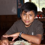 A young boy pauses during lunch.