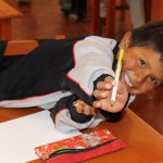 A boy shows off his pencil.