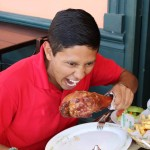 Alejandro demonstrates his willingness to eat a whole turkey leg.