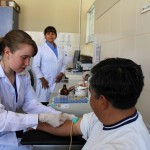 Leah draws a blood sample from Peru SST Service Coordinator Willy Villavicencio.