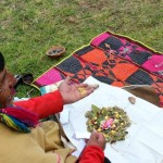 The shaman adds symbolic items to the offering.