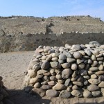 A pile of stones serves as a wind breaker near the central pyramid.