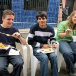 Max, Armando, and Adriene eat anticuchos.