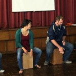 Mariah and fellow students, Shina and Bryan, learn to play the cajon with Camilo Ballumbrosio.