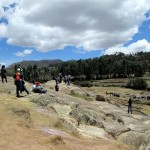 Students explore the rocks at Sacsayhuamán.