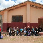 Students sit in front of the first Mennonite Church in Peru in the town of Lucre.