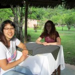 Shina and Laura sit at a table near their bungalow where guests may be served breakfast.