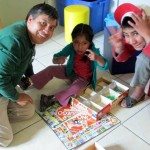 Willy playing Peruvian Monopoly with two children at San Francisco school.
