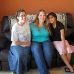 Adriene poses with her host 'aunt' - Jamie - and her host sister, Marleny, in their living room.