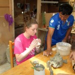 Edgar helps Courtney figure out how to work with a clay mold that he created.
