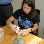 Lea works with a clay mold.