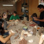 Students concentrate on their clay molds, while artisan assistants paint in the background.