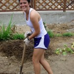 Maria uses a shovel to work the soil.