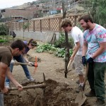 Students take turns working mulch into the soil.