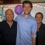 Micah poses with his host parents, Percy and Sonia.