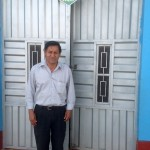 Pastor Romulo in front of the family's church and comedor.