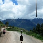 On the bus to Moray, a woman walks along the dirt road with her donkey.