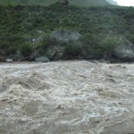 Water running fast and rough in the Urubamba River alongside the train.