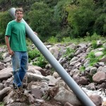 Micah with a section of plastic pipe that will channel water from the river to the pools of the trout farm.