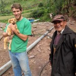 "Micah with a family puppy, ""Gringo"" and his host grandfather, Viktor."